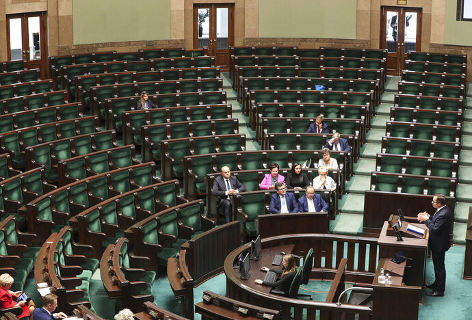 A lawmaker from Poland's ruling party addresses an almost empty lower house during the last session of parliament before Oct.13 general election,in Warsaw, Poland, Wednesday, Sept. 11, 2019. In an unprecedented move, the ruling party is having the session recess until after the election, raising questions about its intentions.(AP Photo/Czarek Sokolowski)