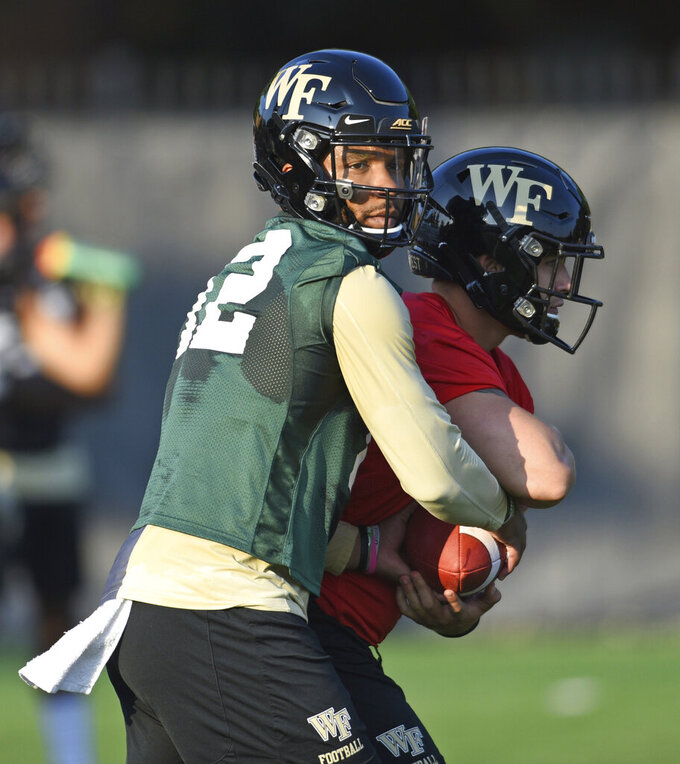 Wake Forest quarterback Jamie Newman takes a snap during the first day of NCAA college football practice in Winston-Salem, N.C., Thursday, Aug. 1, 2019. (Walt Unks/Winston-Salem Journal via AP)