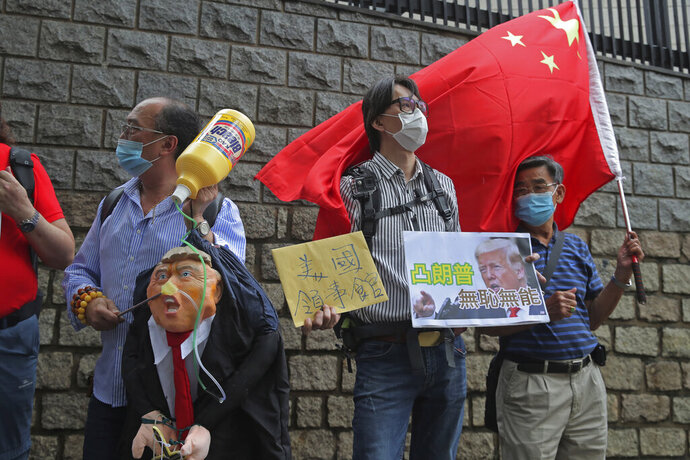 Pro-China supporters hold the effigy of U.S. President Donald Trump and Chinese national flag outside the U.S. Consulate during a protest, in Hong Kong, Saturday, May 30, 2020. President Donald Trump has announced a series of measures aimed at China as a rift between the two countries grows. He said Friday that he would withdraw funding from the World Health Organization, end Hong Kong's special trade status and suspend visas of Chinese graduate students suspected of conducting research on behalf of their government. The placard reads