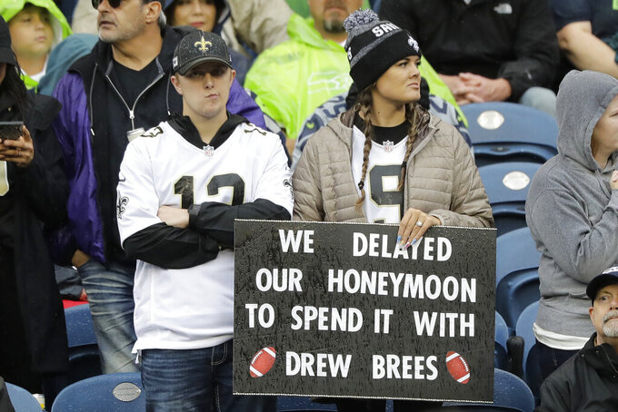 "Two fans hold a sign that reads ""We delayed our honeymoon to spend it with Drew Brees"" in reference to injured New Orleans Saints quarterback Drew Brees before an NFL football game between the Seattle Seahawks and the Saints, Sunday, Sept. 22, 2019, in Seattle. Brees did not play in the game but the Saints won. (AP Photo/Ted S. Warren)"