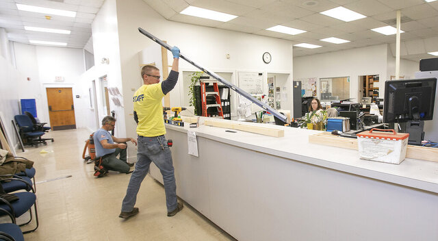 Town crews work to construct new counter windows in the land uses offices on the ground floor of Wallingford Town Hall, Wednesday, March 25, 2020. (Dave Zajac/Record-Journal via AP)
