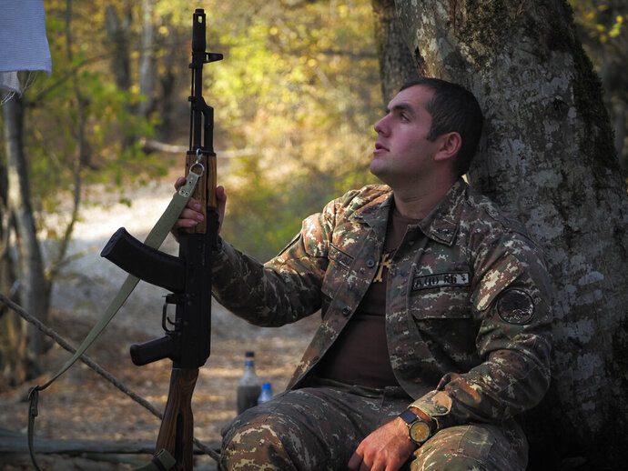 A volunteer soldier holds his Kalashnikov weapon as he rests near a front line at a military base during a military conflict in the separatist region of Nagorno-Karabakh, Tuesday, Oct. 27, 2020. Fighting over Nagorno-Karabakh is raging, unimpeded by a U.S.-brokered cease-fire, while Armenia and Azerbaijan are trading blame for the deal's quick unraveling. (AP Photo)