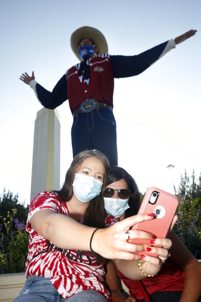 "Oklahoma fans Emily Boyers, of Fort Smith, Ark., and her mother Lisa Martin, of Muldrow, Okla., take a selfie in front of ""Big Tex"" prior an NCAA college football game between the University of Texas and Oklahoma. in Dallas,  Saturday, Oct. 10, 2020. (AP Photo/Michael Ainsworth)"