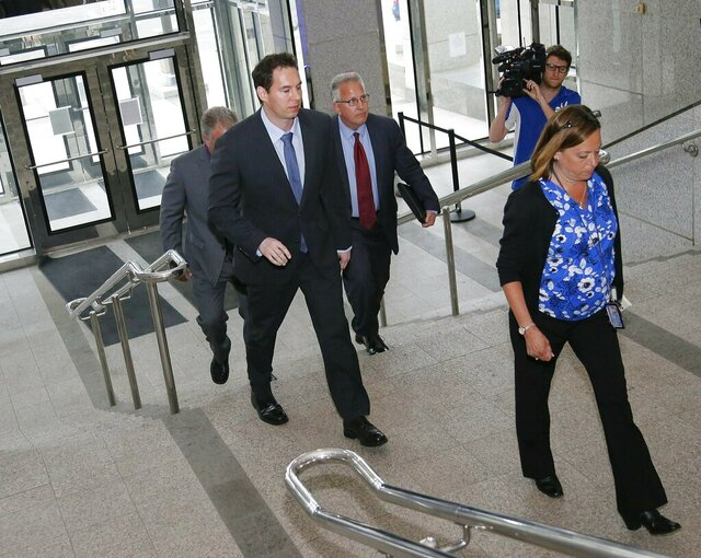 FILE—In this file photo from June 5, 2019, former Dr. William Husel, center, arrives at the downtown Columbus Division of Police headquarters in Columbus, Ohio. An Ohio hospital system has reached more settlements related to Husel, who is accused of ordering excessive painkillers for dozens of patients and has pleaded not guilty to 25 counts of murder. The related settlements involving the Columbus-area Mount Carmel Health System now total more than $16.7 million. That includes three settlements of $750,000 each that were filed in the past two weeks. (Adam Cairns/The Columbus Dispatch via AP, File)