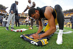 In this Dec. 1, 2019 file photo Pittsburgh Steelers free safety Minkah Fitzpatrick, right, signs his game jersey to swap with Cleveland Browns linebacker Tae Davis (51) following a Steelers win in an NFL football game in Pittsburgh. Fitzpatrick's arrival in Pittsburgh last fall turned a pretty good defense into one of the NFL's best. His goal for an encore after earning All-Pro status? Helping Pittsburgh return to the playoffs. (AP Photo/Gene J. Puskar, File)