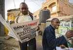 A man reads a copy of a newspaper which managed to print the news of the postponement in time, in the morning at a newspaper stand in Kano, in northern Nigeria Saturday, Feb. 16, 2019. Nigeria's electoral commission delayed the presidential election until Feb. 23, making the announcement a mere five hours before polls were set to open Saturday. (AP Photo/Ben Curtis)