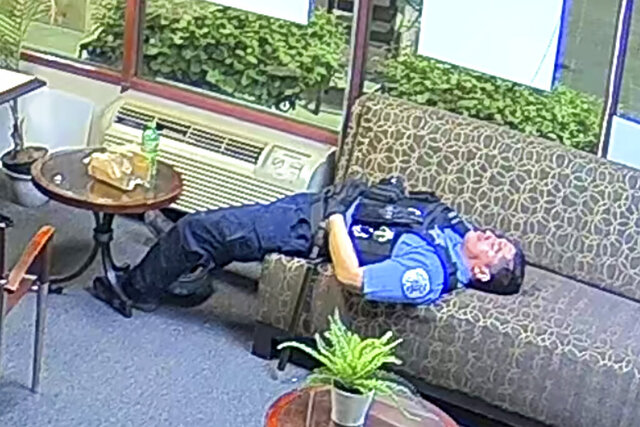 FILE - In this file still image taken from security video released by the Congressman Bobby Rush's Campaign Office, a Chicago police officer lies on a couch inside Rush's burglarized congressional campaign office in Chicago on Sunday, May 31, 2020. Chicago Police suspended several officers captured on video during 2020's widespread unrest who were lounging, and apparently even sleeping, inside a burglarized congressional campaign office as people citywide vandalized and stole from businesses, a police union official said, Thursday, Jan. 14, 2021. (Congressman Bobby Rush's Campaign Office via AP, File)