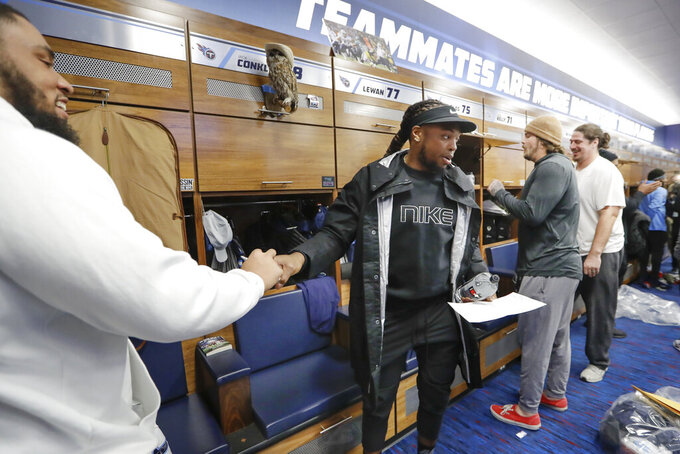 Tennessee Titans running back Derrick Henry, center, hands a pen back to offensive guard Jamil Douglas, left, after autographing an item as players clean out their lockers Monday, Jan. 20, 2020, in Nashville, Tenn. The Titans lost the AFC Championship NFL football game Sunday to the Kansas City Chiefs. (AP Photo/Mark Humphrey)