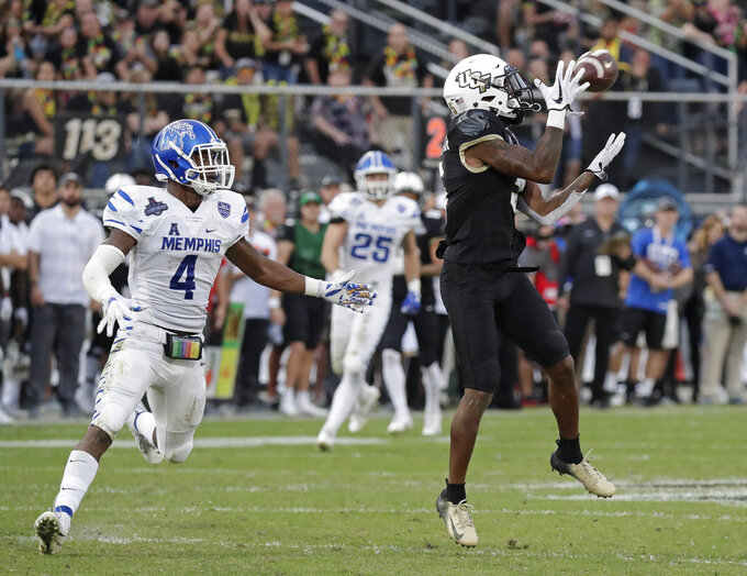 Central Florida wide receiver Dredrick Snelson, right, makes a reception in front of Memphis defensive back Josh Perry (4) during the first half of the American Athletic Conference championship NCAA college football game, Saturday, Dec. 1, 2018, in Orlando, Fla. (AP Photo/John Raoux)
