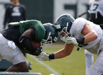 Michigan State running back Alante Thomas, left, and linebacker Ed Warinner collide as they run a drill during an NCAA college football practice, Monday, Aug. 12, 2019, in East Lansing, Mich. (AP Photo/Al Goldis)