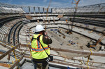 A photographer takes a photo of the new NFL Los Angeles Stadium while under construction during a topping-out ceremony in Inglewood, Calif. on Monday April 15, 2019. Stadium officials hosted a tour for the media after the final piece of the canopy structure to hold the roof was completed. (AP Photo/Richard Vogel)