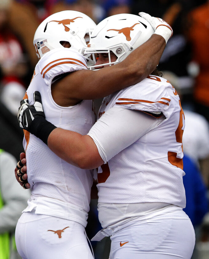 Texas wide receiver Collin Johnson, left, is congratulated by teammate Zach Shackelford, right, after a touchdown during the first half of an NCAA college football game against Kansas in Lawrence, Kan., Friday, Nov. 23, 2018. (AP Photo/Orlin Wagner)