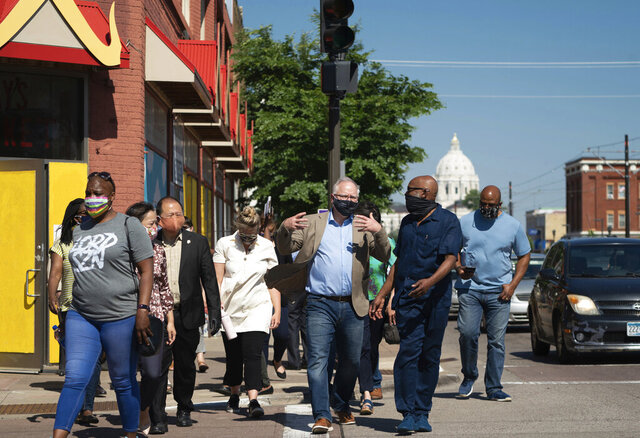 Minnesota Gov. Tim Walz, center, takes a walking tour of some of the artworks commissioned by Springboard for the Arts along University Avenue in St. Paul, Minn., Monday, June 8, 2020. (Glen Stubbe/Star Tribune via AP, Pool)
