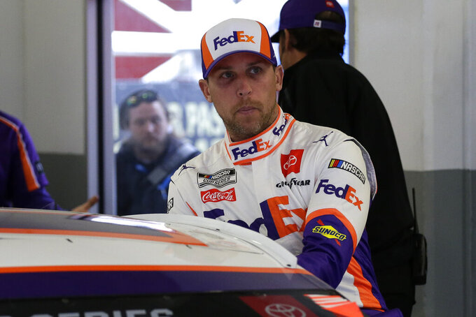 FILE - In this Feb. 14, 2020, file photo, Denny Hamlin climbs into his car as he gets ready to practice for the NASCAR Daytona 500 auto race at Daytona International Speedway in Daytona Beach, Fla. Hamlin is starting his own race car team in partnership with Charlotte Hornets owner Michael Jordan and Bubba Wallace as the driver. (AP Photo/Terry Renna, File)