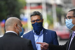 Wearing a mask due to the COVID-19 pandemic, lawyer Jesus Loreto waits with others outside the Supreme Court building where six detained Citgo directors, some of whom he represents, will go on trial on corruption charges in Caracas, Venezuela, Thursday, Aug. 6, 2020. The six men were called to Caracas just before Thanksgiving in 2017 for a meeting at the headquarters of Citgo's parent, Venezuela's state-run oil giant PDVSA, and hauled away from a meeting by masked security agents. (AP Photo/Matias Delacroix)