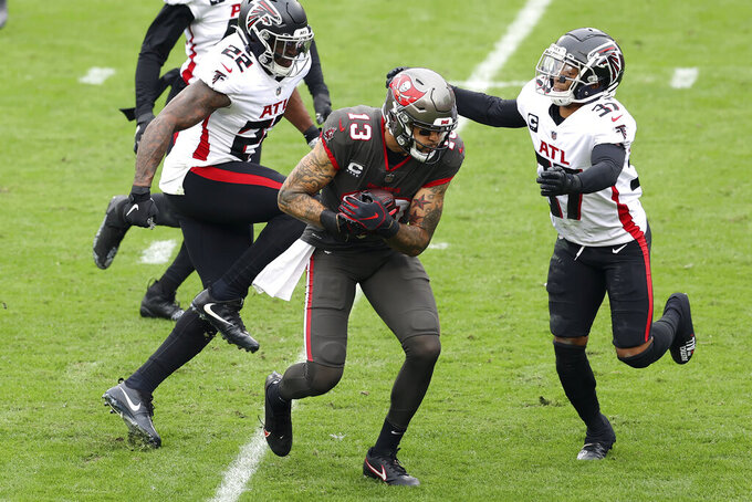 Tampa Bay Buccaneers wide receiver Mike Evans (13) splits between Atlanta Falcons strong safety Keanu Neal (22) and free safety Ricardo Allen (37) after a catch during the first half of an NFL football game Sunday, Jan. 3, 2021, in Tampa, Fla. The catch put Evans over the 1,000 yard total for the season. (AP Photo/Mark LoMoglio)