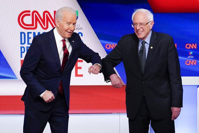 Former Vice President Joe Biden, left, and Sen. Bernie Sanders, I-Vt., right, greet each other before they participate in a Democratic presidential primary debate at CNN Studios in Washington, Sunday, March 15, 2020. (AP Photo/Evan Vucci)