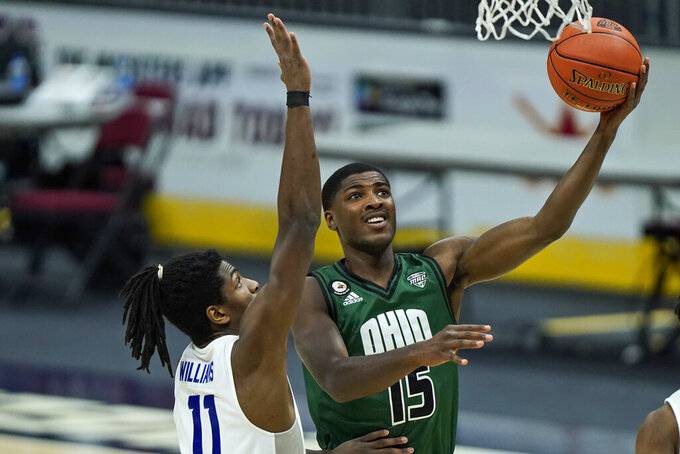 Ohio's Lunden McDay (15) drives to the basket against Buffalo's Jeenathan Williams (11) during the first half of an NCAA college basketball game in the championship of the Mid-American Conference tournament, Saturday, March 13, 2021, in Cleveland. (AP Photo/Tony Dejak)