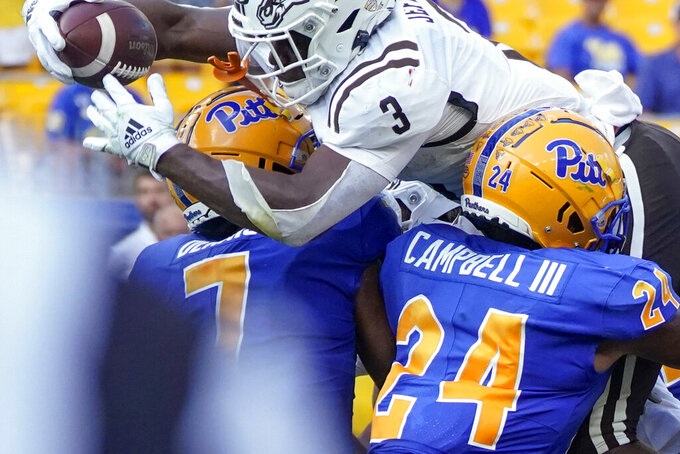 Western Michigan running back La'Darius Jefferson (3) goes over Pittsburgh linebackers Phil Campbell III (24) and SirVocea Dennis (7) for a touchdown during the first half of an NCAA college football game, Saturday, Sept. 18, 2021, in Pittsburgh. (AP Photo/Keith Srakocic)