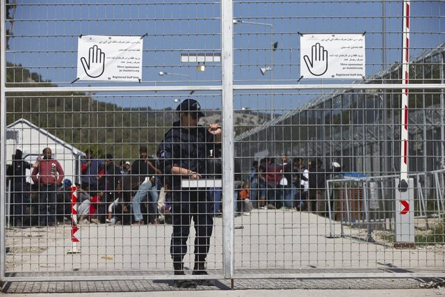 FILE - In this Tuesday, April 5, 2016 file photo, a Greek police officer closes the main gate of Moria camp as behind her refugees and migrants protest against the EU- Turkey deal about migration inside the entrance of Moria camp in the Greek island of Lesbos. Greece's government says on Monday, Feb. 10, 2020 it is planning to use emergency legal powers to create detention centers for migrants on five Greece islands to try and speed up deportations back to Turkey. (AP Photo/Petros Giannakouris, File)