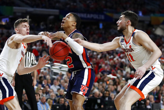 Auburn guard J'Von McCormick, center, drives to the basket between Virginia's Kyle Guy, left, and Ty Jerome, right, during the second half in the semifinals of the Final Four NCAA college basketball tournament, Saturday, April 6, 2019, in Minneapolis. (AP Photo/Jeff Roberson)