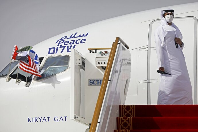 "FILE - In this Monday, Aug. 31, 2020 file photo, an official stands at the door of an Israeli El Al airliner after it landed in Abu Dhabi, United Arab Emirates. The Saudi Press Agency announced Wednesday, Sept. 2, 2020, that it will allow flights ""from all countries"" to cross its skies to reach the United Arab Emirates. The announcement comes just days after Saudi Arabia allowed the first direct Israeli commercial passenger flight to use its airspace to reach the UAE, signaling acquiescence for a breakthrough U.S.-brokered deal by the United Arab Emirates to normalize relations with Israel. (Nir Elias/Pool Photo via AP, File)"