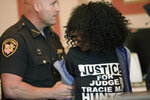 A woman is taken into custody after jumping the rail after former judge Tracie Hunter was ordered to serve her sentence of six-months in jail by Judge Patrick T. Dinkelacker on Monday, July 22, 2019 in Cincinnati. Hunter, 52, had gone to multiple courts to challenge her 2014 conviction and sentence on a felony count of unlawful interest in a public contract, which charged that she provided a confidential document to her brother when he faced a disciplinary hearing in his court job. (Albert Cesare/The Cincinnati Enquirer via AP)