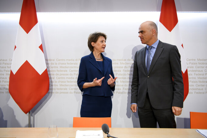 Swiss Federal president Simonetta Sommaruga, left, and Swiss Federal councillor Alain Berset, right, talk after the media briefing about the latest measures to fight the Covid-19 Coronavirus pandemic in Bern, Switzerland, Monday, March 16, 2020. The vast majority of people recover from the new coronavirus, according to the World  Health Organization, most people recover in about two to six weeks, depending on the severity of the illness.(Anthony Anex/Keystone via AP)