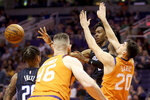 Orlando Magic's Wes Iwundu, back right, passes the ball after running into Phoenix Suns' Dario Saric (20) during the first half of an NBA basketball game Friday, Jan. 10, 2020, in Phoenix. (AP Photo/Darryl Webb)