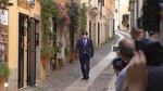 Catalan separatist leader Carles Puigdemont walks in a street of the Sardinian city of Alghero, Italy, Saturday, Sept. 25, 2021, a day after a judge freed him from jail pending a hearing on his extradition to Spain, where the political firebrand is wanted for sedition. (AP Photo/Andrea Rosa)