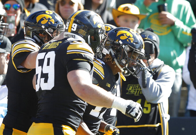 Iowa wide receiver Brandon Smith, right, celebrates with teammates after catching a 10-yard touchdown pass during the first half of an NCAA college football game against Maryland, Saturday, Oct. 20, 2018, in Iowa City, Iowa. (AP Photo/Charlie Neibergall)