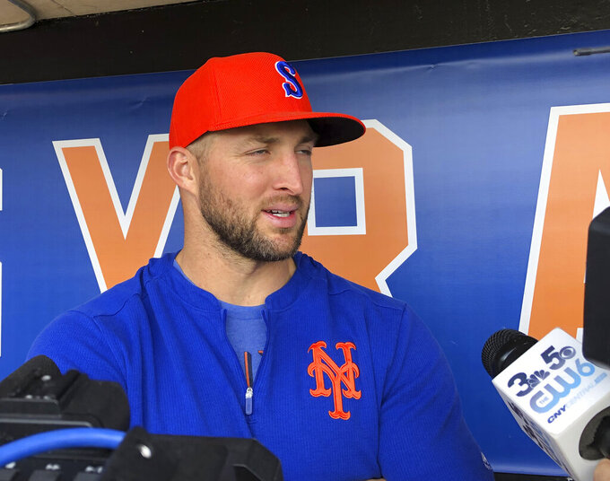FILE - In this May 16, 2019 file photo, Syracuse Mets' Tim Tebow speaks with reporters prior to a minor league baseball game in Syracuse, N.Y.  Tebow has been invited to big league spring training by the New York Mets, taking one of 75 spots after Major League Baseball limited spring roster sizes as a coronavirus precaution.   (AP Photo/John Kekis, File)