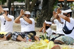 Balinese men pray during a ritual at Kuta beach, Bali, Indonesia on Thursday, July 9, 2020. Indonesia's resort island of Bali reopened after a three-month virus lockdown Thursday, allowing local people and stranded foreign tourists to resume public activities before foreign arrivals resume in September.(AP Photo/Firdia Lisnawati)