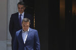 Greece's newly-elected prime minister Kyriakos Mitsotakis, background, looks on as outgoing prime minister Alexis Tsipras, leaves the Maximos Mansion in Athens, Monday, July 8, 2019. Mitsotakis' New Democracy party won 39.8% of the vote, giving him 158 seats in the 300-member parliament, a comfortable governing majority. (AP Photo/Petros Giannakouris)