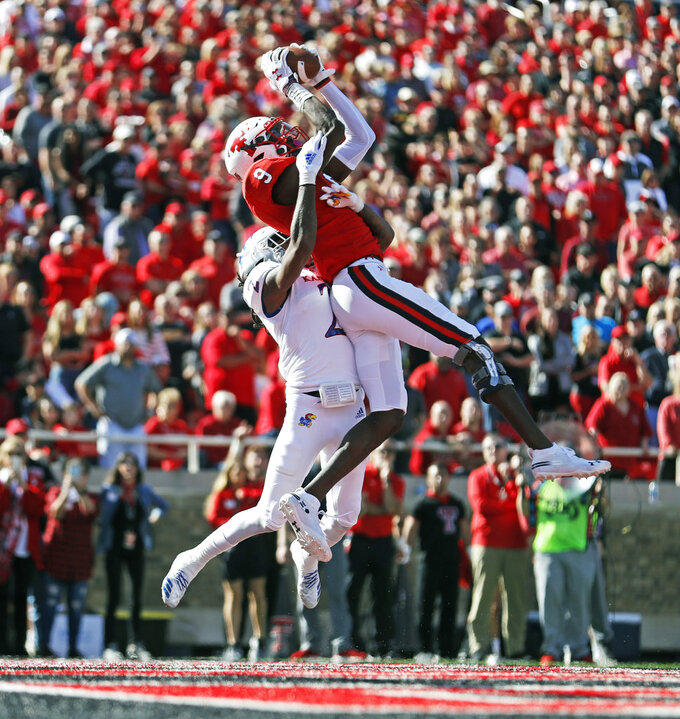 Texas Tech's T.J. Vasher (9) catches a touchdown pass over Kansas' Corione Harris (2) during the first half of an NCAA college football game Saturday, Oct. 20, 2018, in Lubbock, Texas. (Brad Tollefson/Lubbock Avalanche-Journal via AP)