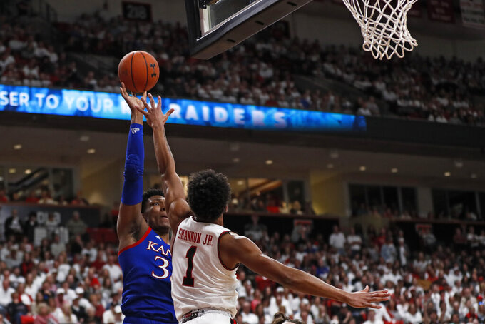 Kansas' David McCormack (33) shoots the ball over Texas Tech's Terrence Shannon Jr. (1) during the first half of an NCAA college basketball game Saturday, March 7, 2020, in Lubbock, Texas. (AP Photo/Brad Tollefson)
