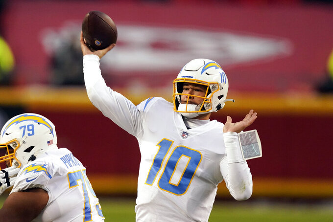 FILE - In this Jan. 3, 2021, file photo, Los Angeles Chargers quarterback Justin Herbert throws a pass during the first half of an NFL football game against the Kansas City Chiefs in Kansas City.  Herbert has had a busy four weeks since the Chargers ended their season, but he already has set his sights on what will be another transitional offseason for him. (AP Photo/Charlie Riedel, File)