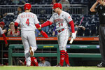 Cincinnati Reds' Jose Iglesias (4) is greeted by on-deck batter Brian O'Grady after scoring on a hit by Michael Lorenzen in the eighth inning of a baseball game against the Pittsburgh Pirates, Friday, Sept. 27, 2019, in Pittsburgh. (AP Photo/Keith Srakocic)
