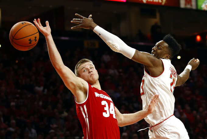 Wisconsin guard Brad Davison, left, and Maryland forward Bruno Fernando, of Angola, reach for a rebound in the second half of an NCAA college basketball game, Monday, Jan. 14, 2019, in College Park, Md. (AP Photo/Patrick Semansky)