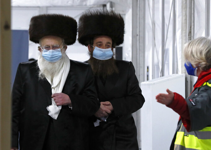 Two men from the Haredi Orthodox Jewish community arrive at an event to encourage vaccine uptake in the ultra-Orthodox community at the John Scott Vaccination Centre in London, Saturday, Feb. 13, 2021. In hopes of breaking down barriers that sometimes isolate the Orthodox from wider society, community leaders organized the pop-up vaccination event for Saturday night to coincide with the end of Shabbat, the Jewish day of rest. (AP Photo/Frank Augstein)
