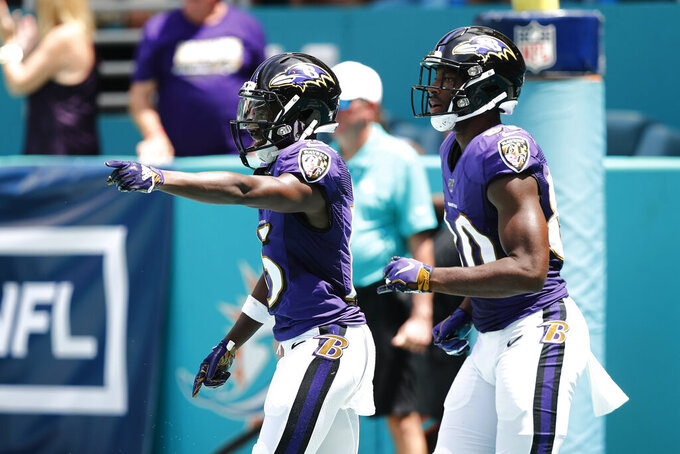 Baltimore Ravens wide receiver Marquise Brown (15) gestures after scoring a touchdown, during the first half at an NFL football game, Sunday, Sept. 8, 2019, in Miami Gardens, Fla. To the right is Baltimore Ravens wide receiver Miles Boykin (80). (AP Photo/Brynn Anderson)