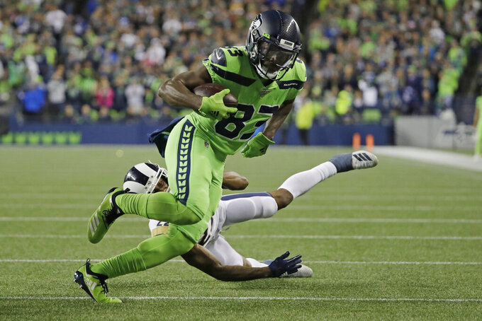 Seattle Seahawks wide receiver David Moore (83) gets past Los Angeles Rams cornerback Marcus Peters to score a touchdown during the second half of an NFL football game Thursday, Oct. 3, 2019, in Seattle. (AP Photo/Elaine Thompson)