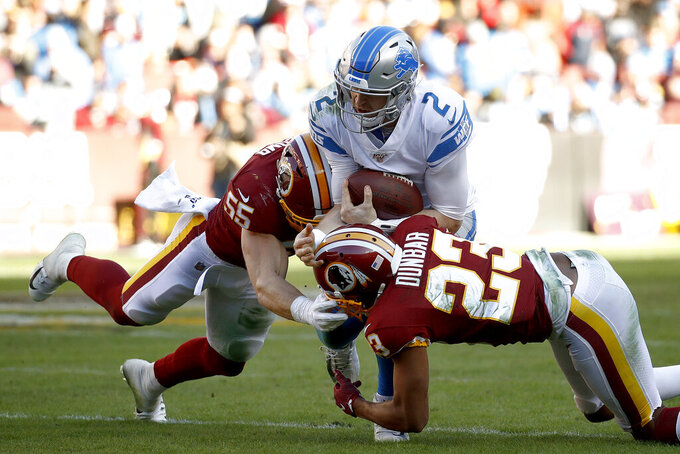 Detroit Lions quarterback Jeff Driskel (2) is tackled by Washington Redskins linebacker Cole Holcomb (55) and cornerback Quinton Dunbar (23) during the first half of an NFL football game, Sunday, Nov. 24, 2019, in Landover, Md. (AP Photo/Patrick Semansky)