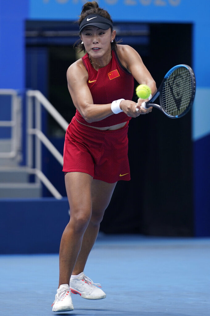 Qiang Wang, of China, plays Garbine Muguruza, of Spain, during the second round of the tennis competition at the 2020 Summer Olympics, Monday, July 26, 2021, in Tokyo, Japan. (AP Photo/Seth Wenig)