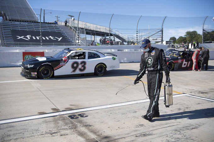 A crew member sprays a chemical so the car tires and pit crew will not slip during a NASCAR Xfinity Series auto race at the Martinsville Speedway in Martinsville, Va., Saturday, Oct.31, 2020. (AP Photo/Lee Luther Jr.)