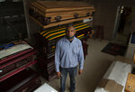 Casey Pillay stands in front of stacked coffins at Enzo Wood Designs, where he's a manager, in Johannesburg, Thursday, Oct. 1, 2020. Pillay watched the coronavirus pandemic turn the coffin-making business upside down. It also moved into his home, infecting his wife, who helped pregnant women with the virus deliver their babies. She later recovered, reflecting the relatively low death toll from COVID-19 in South Africa, and in Africa in general. (AP Photo/Denis Farrell)