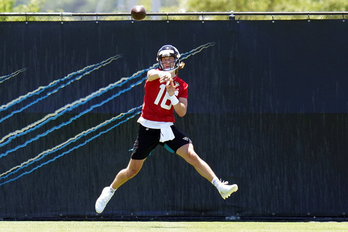 Jacksonville Jaguars quarterback Trevor Lawrence (16) throws a pass during an NFL football rookie minicamp, Saturday, May 15, 2021, in Jacksonville, Fla. (AP Photo/John Raoux)