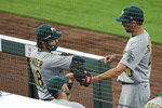 Oakland Athletics starting pitcher Chris Bassitt, right, greets teammates in the dugout after he was pulled during the sixth inning of a baseball game against the Seattle Mariners, Sunday, Aug. 2, 2020, in Seattle. (AP Photo/Ted S. Warren)