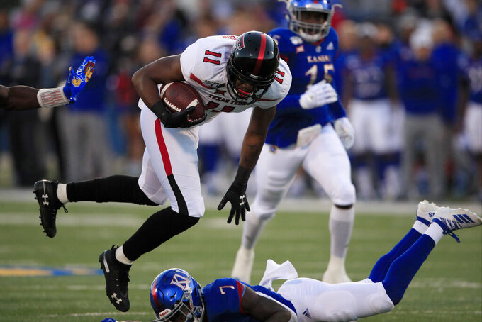 Texas Tech tight end Donta Thompson (11) jumps over Kansas safety Davon Ferguson (7) during the first half of an NCAA college football game in Lawrence, Kan., Saturday, Oct. 26, 2019. (AP Photo/Orlin Wagner)