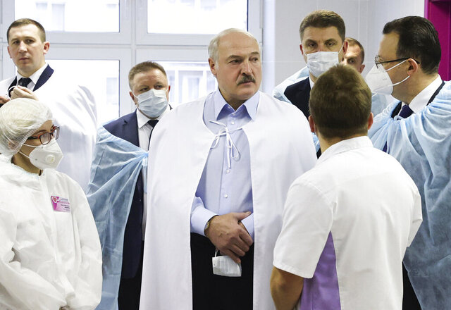 Belarusian President Alexander Lukashenko, centre, listens to medics as he visits a transfusiology center in Minsk, Belarus, Friday, Nov. 27, 2020. (Maxim Guchek/BelTA Pool Photo via AP)